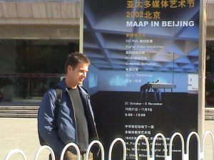 Artist, Craig Walsh outside the China Millennium Monument Art Museum, Beijing standing with the exhibition's poster featuring his art work. 22 October 2002.