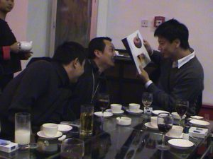 Curator PiLi, with artists Wang Gongxin and Zhu Jia looking at the 'MAAP in Beijing' catalogue at the after opening dinner celebration. October 2002